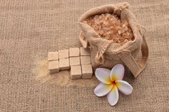 Sugar and Plumeria flower on hemp sackcloth  background. Selective focus with shallow depth of field Stock Images