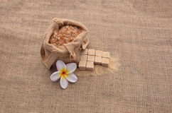 Sugar and Plumeria flower on hemp sackcloth  background. Selective focus with shallow depth of field Stock Photo