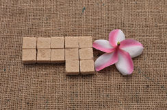 Sugar and Plumeria flower on hemp sackcloth  background. Selective focus with shallow depth of field Stock Photos