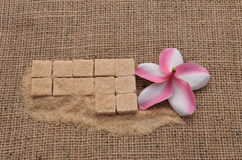 Sugar and Plumeria flower on hemp sackcloth  background. Selective focus with shallow depth of field Royalty Free Stock Photos