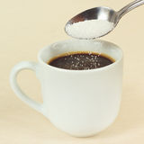 Sugar is poured from a spoon in coffee cup Royalty Free Stock Images