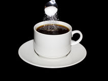 Sugar is poured from a spoon into a cup of coffee Royalty Free Stock Images