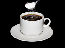 Sugar is poured from a spoon into a cup of coffee Stock Image