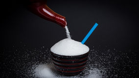 Sugar. Pouring sugar into a little cup in front of black background - Concept of sugary drinks Stock Photo