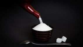 Sugar. Pouring sugar into a little cup in front of black background - Concept of sugary drinks Stock Photos