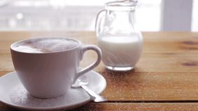 Sugar pouring to coffee cup on wooden table. Unhealthy eating, diabetes, object and drinks concept - white sugar pouring to coffee cup on wooden table with cream stock video
