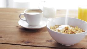 Sugar pouring to corn flakes on wooden table stock footage