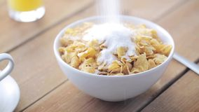 Sugar pouring to corn flakes on wooden table. Breakfast, food, objects and unhealthy eating concept - white sugar pouring to corn flakes on wooden table stock video