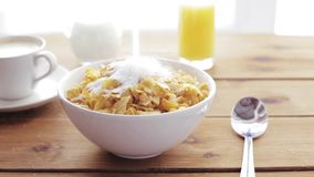 Sugar pouring to corn flakes on wooden table. Breakfast, food, objects and unhealthy eating concept - white sugar pouring to corn flakes on wooden table stock footage