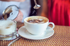 Sugar pours from spoon in the coffee, man and woman holding cups, with hearts in cafe Stock Photos