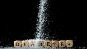 Sugar powder being poured over dice spelling out diabetes