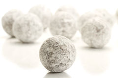 Sugar powder covered truffle praline in front of m Royalty Free Stock Photography