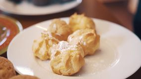 Sugar powder pour on profiteroles on table with lots of baking products