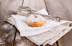 Sugar powdered cinnamon doughnut on baking paper on rustic wooden background close up. Freshly baked cinnamon sugared doughnuts on baking paper and linen napkin stock photo