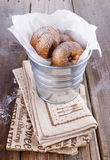 Sugar powdered cinnamon doughnuts in a metal bucket on rustic wooden background close up. Freshly baked cinnamon sugared doughnuts in wrapping paper in the metal stock photography