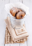 Sugar powdered cinnamon doughnuts in a metal bucket on white wooden background. Freshly baked cinnamon sugared doughnuts in wrapping paper in the metal bucket on royalty free stock photo