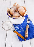 Sugar powdered cinnamon doughnuts in a metal rusti. Freshly baked cinnamon sugared doughnuts in a metal rustic bowl on a blue napkin with sieve and fork on white stock photos