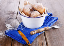 Sugar powdered cinnamon doughnuts in a metal rustic bowl on rustic wooden background with sieve. Freshly baked cinnamon sugared doughnuts in a metal rustic bowl royalty free stock photos