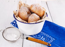 Sugar powdered cinnamon doughnuts in a metal rustic bowl on white wooden background with sieve close up. Freshly baked cinnamon sugared doughnuts in metal rustic royalty free stock photo