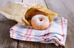 Sugar powdered cinnamon doughnuts in paper bag on rustic wooden background. Freshly baked cinnamon sugared doughnuts in paper bag on the checked kitchen towel on royalty free stock photo