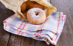 Sugar powdered cinnamon doughnuts in paper bag on rustic wooden background. Freshly baked cinnamon sugared doughnuts in paper bag on the pleated kitchen towel on royalty free stock image