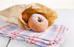 Sugar powdered cinnamon doughnuts in paper bag on white wooden background. Freshly baked cinnamon sugared doughnuts in paper bag on the checked kitchen towel on royalty free stock images