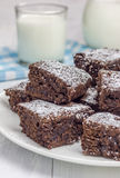 Sugar powdered homemade brownies with glass of milk. Closeup Stock Photography