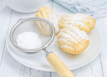 Sugar powdered madeleines on the white plate. Closeup Stock Photo