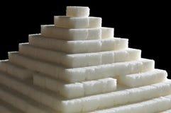 Sugar pyramid. Pyramid made of sugar cubes on black background stock photos