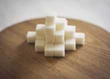 Sugar refined on a brown wooden board. The refined sugar is packed in cubes. The geometric figure is made of sugar. Sweet mood. A lot of sugar. Mountain of Royalty Free Stock Image