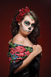 Sugar scar. Woman in makeup for Dia De Los Muertos with roses in her hair Stock Photos