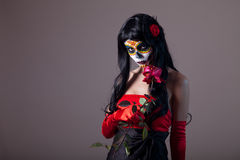 Sugar skull girl holding red rose. Day of the Dead Halloween theme stock image