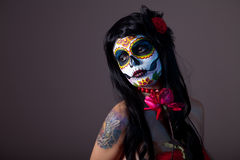 Sugar skull girl with red rose. Professional body-art royalty free stock photography