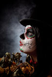 Sugar skull woman in tophat, holding dead roses. Studio shot Royalty Free Stock Image