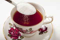 Sugar Spilling Into Teacup Royalty Free Stock Photography