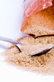 Sugar and spoon. A mound of packaged brown sugar with a spoon Royalty Free Stock Photo