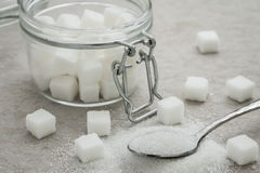 Sugar on spoon and glass jar Stock Image