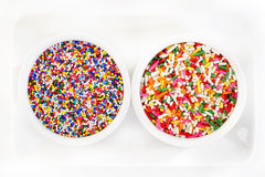 Sugar spreading and rainbow sprinkles Stock Images