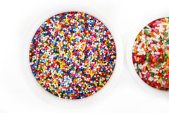 Sugar spreading and rainbow sprinkles in cup on white Stock Image