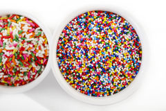 Sugar spreading and rainbow sprinkles in cup on white Royalty Free Stock Images