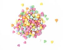 Sugar sprinkle dots hearts, decoration for cake and bakery. Colorful sugar sprinkles scattered on white background. Copy space for text stock photography