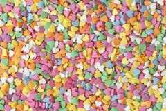 Sugar sprinkle dots hearts, decoration for cake and bakery. Colorful sugar sprinkles scattered on white background. Copy space for text stock images