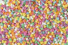 Sugar sprinkle dots hearts, decoration for cake and bakery. Colorful sugar sprinkles scattered on white background. Copy space for text royalty free stock photos