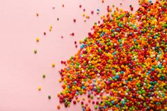 Colorful sprinkles scattered on pink background stock images