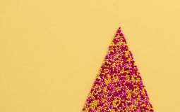 Sugar sprinkle dots in the shape of a Christmas tree on yellow background,decoration for cake and bakery stock photo