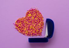 Sugar sprinkle dots in the shape of a heart and ring box on purple background,decoration for wedding.  royalty free stock photography