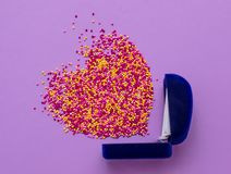 Sugar sprinkle dots in the shape of a heart and ring box on purple background,decoration for wedding.  royalty free stock image