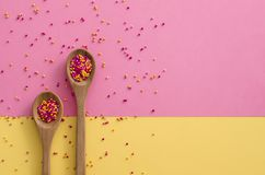 Sugar sprinkle dots In a wooden spoon on pink and yellow background,decoration for cake and bakery stock photography