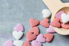 Sugar Sprinkles Candies Spilled blanco rosado colorido de la pequeña cuchara de madera en Grey Background valentines fotografía de archivo