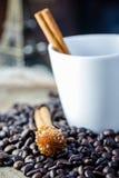 Sugar Stick Cinnamon en el café de la taza y el grano de café blancos Foto de archivo